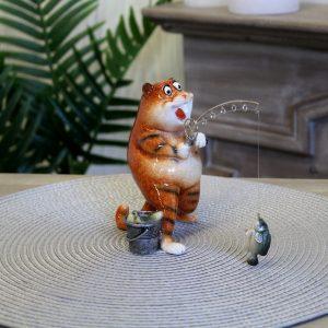 Grappig beeldje van een rode kat die een vis aan de hengel heeft .